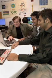 Image of an instructor helping students with their work.