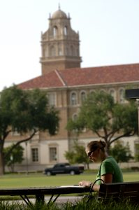 Image of a Texas Tech Unviersity student studying outdoors on campus.