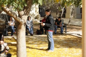 Image of student practicing a presentation outdoors on campus.