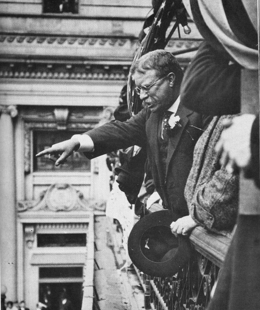 Teddy Roosevelt pointing at the crowd outside a balcony