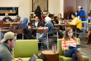 Students studying in groups on campus while multitasking.